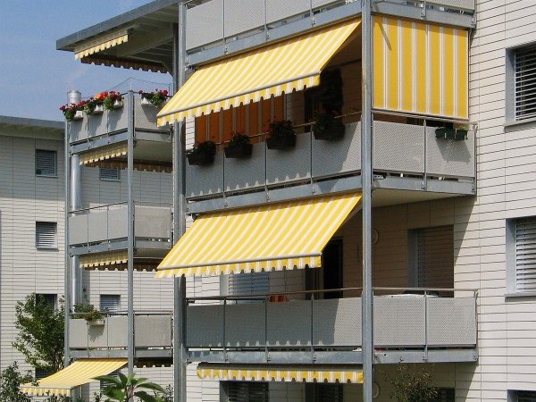 Yellow and white striped retractable awnings for decks, from Leavitt & Parris