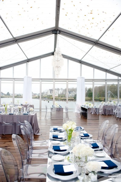 A clear top structure and clear chairs make a dramatic impact at a Maine wedding